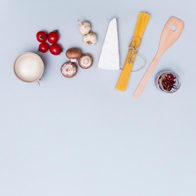 Käse; frisches gemüse und weiße sauce für die herstellung von spaghetti nudeln auf grauer oberfläche Kostenlose Fotos