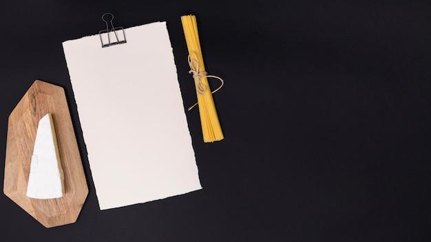 Käse; spaghettiteigwaren und weißes leeres papier auf schwarzem hintergrund Kostenlose Fotos
