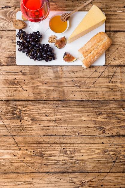 Käse, wein, stangenbrottraubenfeigenhonig und snäcke auf die rustikale holztischoberseite mit kopienraum. Premium Fotos