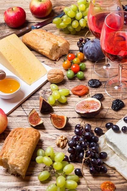 Käse-, wein-, stangenbrottraubenfeigenhonig und snäcke auf die rustikale holztischoberseite. Premium Fotos