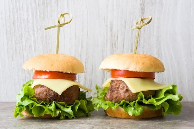 Käseburger mit gemüse auf holztisch Premium Fotos