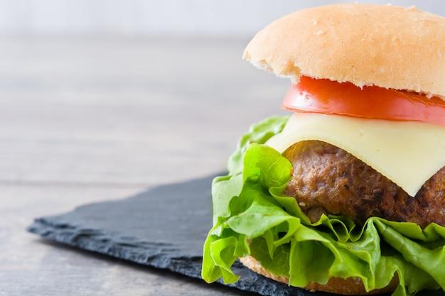 Käseburger mit gemüse auf holztischkopienraum Premium Fotos