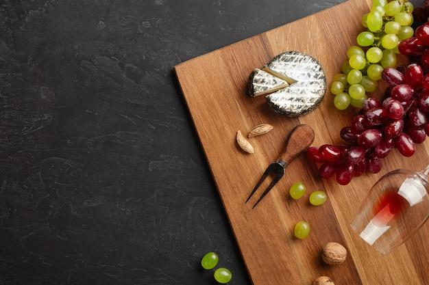 Käsekopf, weintraube, honig, nüsse und weinglas auf hölzernem brett und schwarzem hintergrund Premium Fotos