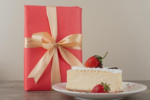 Käsekuchen mit erdbeeren und ein geschenk auf marmortisch Kostenlose Fotos