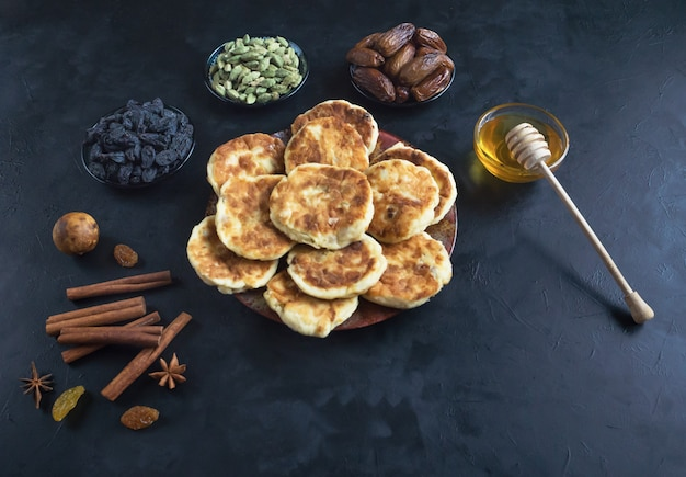 Käsekuchen mit honig, datteln und kaffee auf dem tisch. Premium Fotos