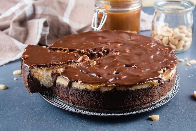 Käsekuchen snickers mit karamell, nougat und erdnuss überlagert kuchen auf blauem konkretem backgro Premium Fotos