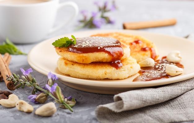 Käsepfannkuchen mit karamellsoße auf einer beige keramischen platte und einem tasse kaffee auf grauem beton Premium Fotos