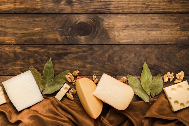 Käsescheibe; lorbeerblätter und walnuss arrangieren am unteren rand des hölzernen hintergrunds mit seidenmaterial textil Kostenlose Fotos