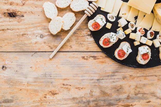 Käsescheiben und brotaperitif mit honigschöpflöffel auf hölzernem schreibtisch Kostenlose Fotos