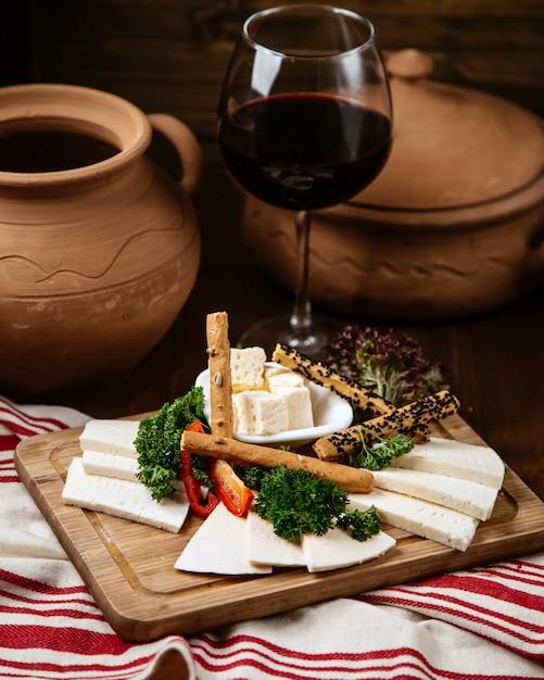 Käseteller mit knusprigem brot und einem glas wein Kostenlose Fotos