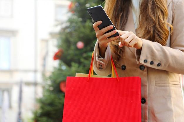Käuferfrau, die smartphone zum online-einkauf und zum tragen von taschen zur weihnachtszeit verwendet. Premium Fotos