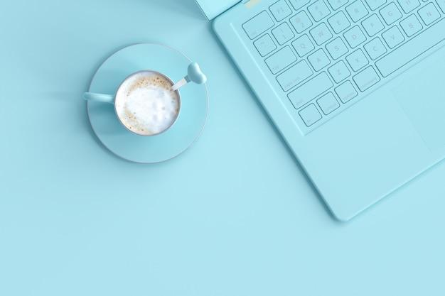Kaffee blaue tasse neben laptop am schreibtisch Premium Fotos
