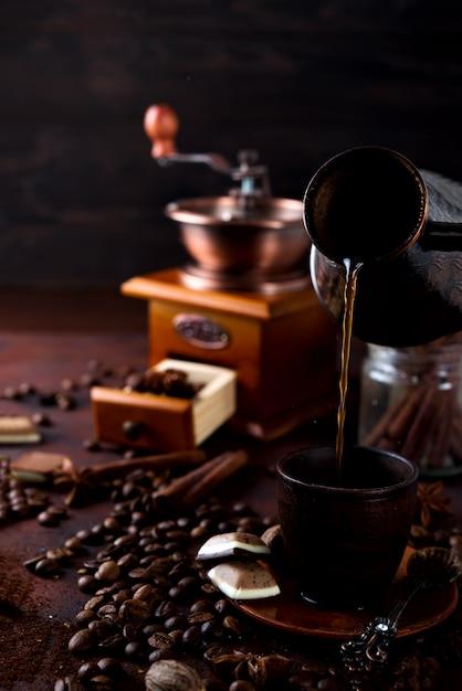 Kaffee gießt zum cup auf dunklem steinhintergrund mit kaffeebohnen Premium Fotos