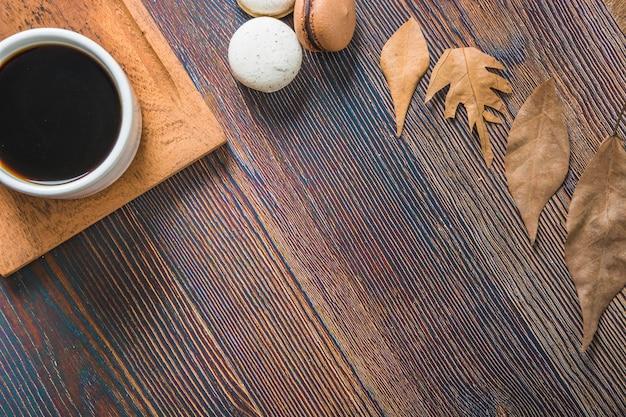 Kaffee in der nähe von blättern und makronen | Kostenlose Foto