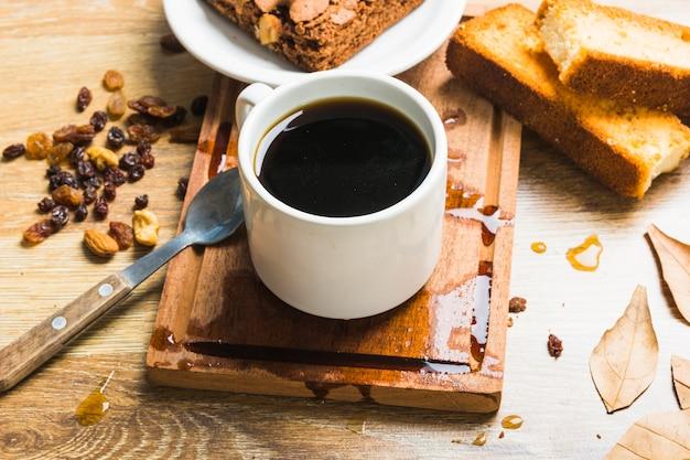 Kaffee in der nähe von gebäck und rosinen | Kostenlose Foto