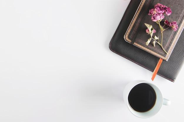Kaffee in der nähe von notizbüchern und blumen ...