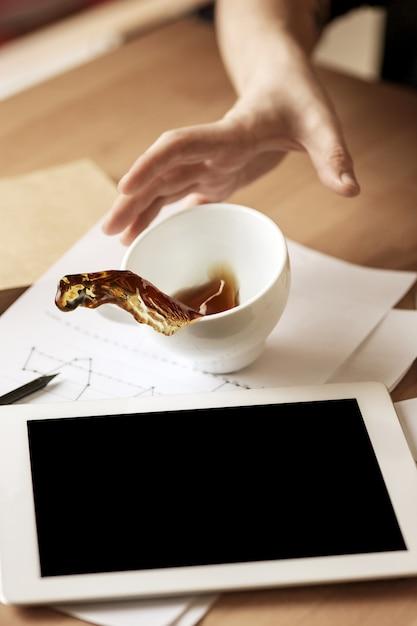 Kaffee in der weißen schale, die morgens auf dem tisch am bürotisch verschüttet wird Kostenlose Fotos