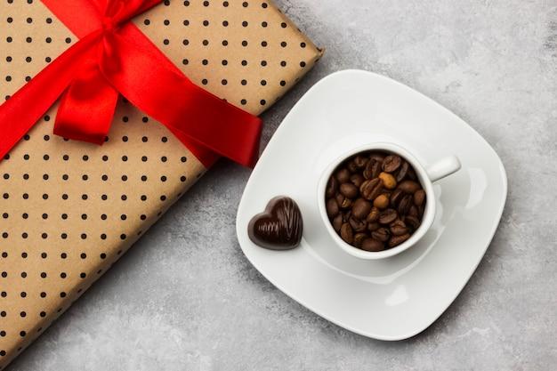 Kaffee in der weißen schale, geschenk mit bürokratie und schokoladen. ansicht von oben. essen hintergrund Premium Fotos
