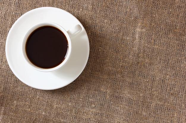 Kaffee in einer tasse und untertasse auf leinentischdecke. ansicht von oben. Premium Fotos