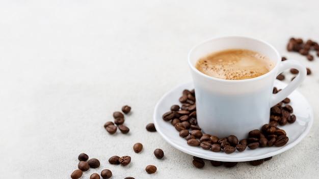 Kaffee in weißer tasse mit bohnen auf teller Kostenlose Fotos