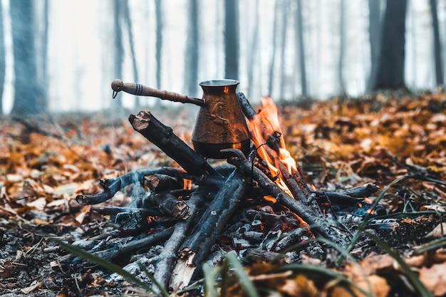 Kaffee kochen auf dem spiel. machen sie kaffee oder tee am feuer der natur. verbranntes feuer. ein ort für feuer. asche und kohle. Premium Fotos