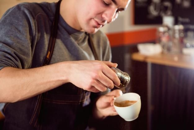 Kaffee latte barista, der muster in einer tasse kaffeestube macht. Premium Fotos