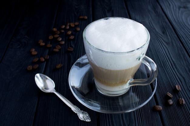 Kaffee latte in der glasschale auf dem schwarzen holztisch Premium Fotos