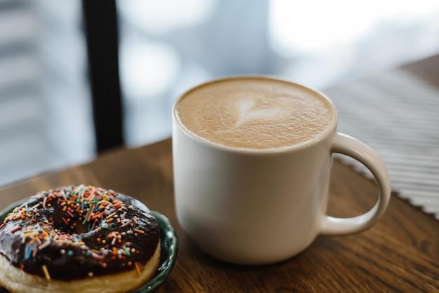 Kaffee mit einem gezogenen herzen und einer milch auf einem holztisch in einer kaffeestube. rosa krapfen mit auf dem tisch zerstreuen nahe bei dem kaffee Premium Fotos