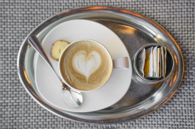 Kaffee mit einem muster auf dem schaum. draufsicht auf einen hellbraunen schaum, ein muster aus milchschaum in form eines herzens. Premium Fotos