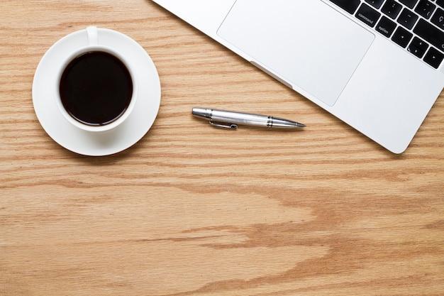 Kaffee neben stift und laptop Kostenlose Fotos
