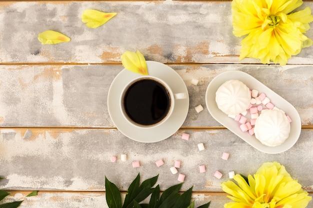 Kaffee und eibische auf hölzerner hintergrundzusammensetzung mit blumen. Premium Fotos