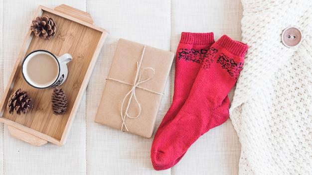 Kaffee und geschenk in der nähe von socken und pullover Kostenlose Fotos