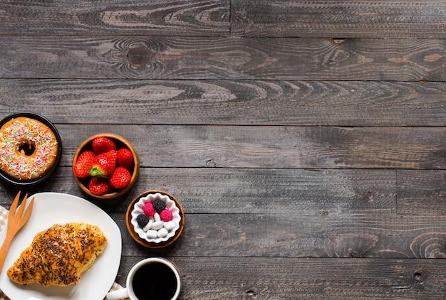 Kaffee und hörnchen zum frühstück auf rustikalem hölzernem hintergrund Premium Fotos