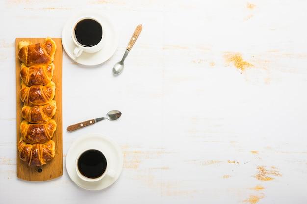 Kaffee und löffel in der nähe von croissants | Kostenlose Foto
