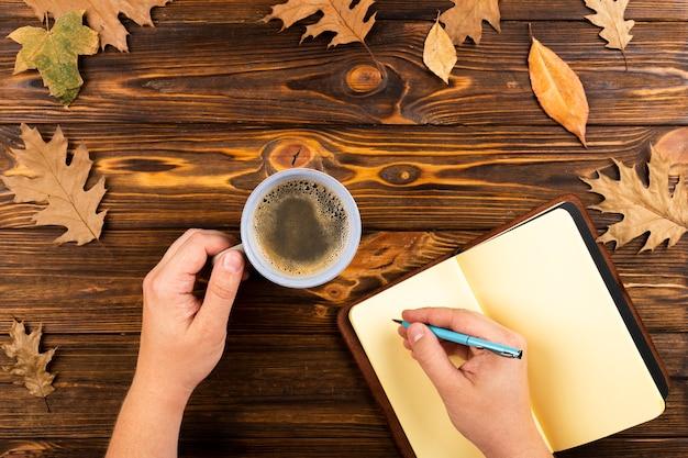Kaffee und notizbuch auf herbstlaubhintergrund Kostenlose Fotos