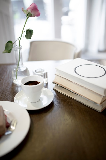 Kaffee und rose in der nähe von büchern | Kostenlose Foto