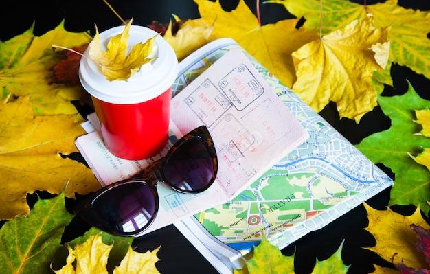 Kaffee zum mitnehmen, blätter, karte, sonnenbrille und reisepass Premium Fotos