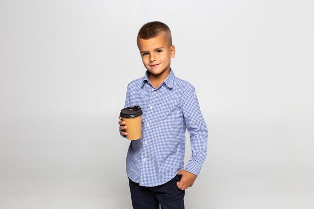 Kaffeebecher des kleinen jungen, der lokalisiert auf weißer wand steht Kostenlose Fotos
