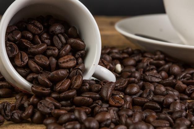Kaffeebohne auf hölzernem hintergrund des schmutzes Premium Fotos
