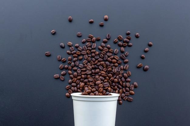 Kaffeebohne in der weißen heißen schale auf schreibtischhintergrund Premium Fotos