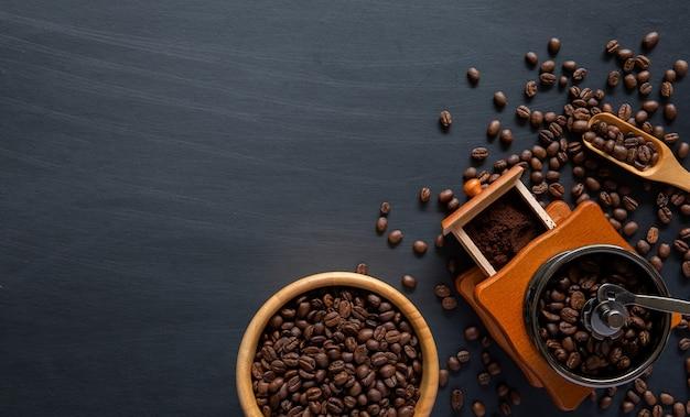 Kaffeebohne und handmühle auf schwarzem tisch. platz für text. Premium Fotos