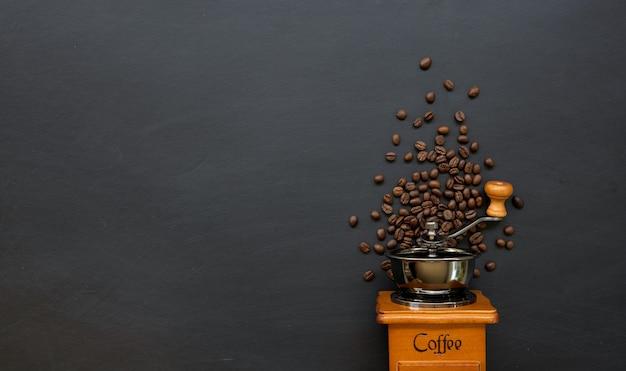 Kaffeebohne und handmühle auf schwarzem tischhintergrund. platz für text. draufsicht Premium Fotos
