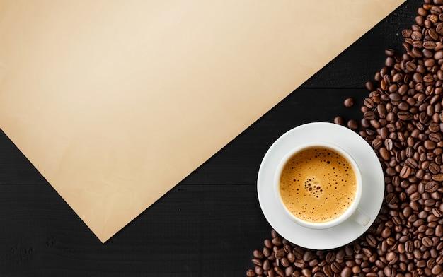 Kaffeebohne und weinlesepapier auf schwarzer hölzerner tabelle Premium Fotos