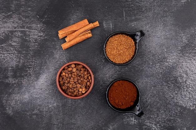 Kaffeebohnekaffeepulverkaffee sofortig und zimt auf schwarzer steinoberfläche Kostenlose Fotos