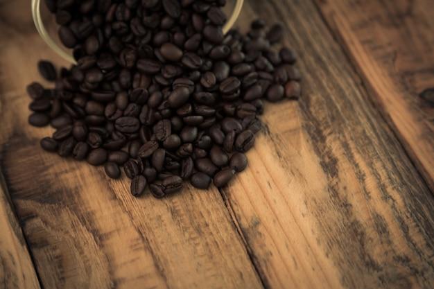 kaffeebohnen auf einem holztisch aus einer sch ssel kommt. Black Bedroom Furniture Sets. Home Design Ideas
