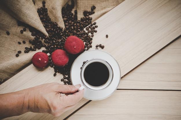 Kaffeebohnen auf leinwandsack mit kaffeejungem und rotem macaron auf hölzernem hintergrund, draufsicht. Premium Fotos