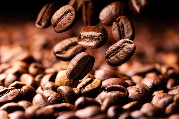 Kaffeebohnen fallen auf haufen Premium Fotos