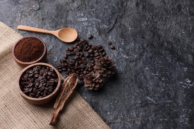 Kaffeebohnen in der hölzernen schale auf leinwand, hölzerner löffel auf schwarzem steinhintergrund Premium Fotos