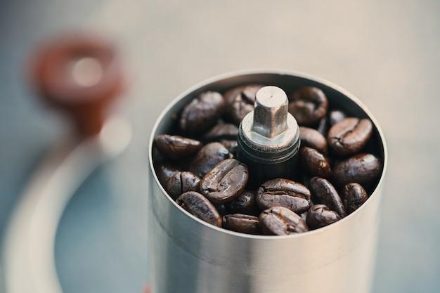 Kaffeebohnen in einer handschleifmaschine, nahaufnahmeröstkaffeebohnen in eine manuelle kaffeemühle Premium Fotos