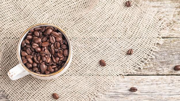 Kaffeebohnen in einer tasse. ansicht von oben Premium Fotos